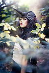 A girl in unicorn style costume in a forest setting