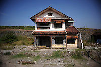 Deserted house with the earthen dam holding back millions of gallons of mud right behind it. The banner reads defiantly: &quot;This house is not for sale&quot;. Since May 2006, more than 10,000 people in the Porong subdistrict of Sidoarjo have been displaced by hot mud flowing from a natural gas well that was being drilled by the oil company Lapindo Brantas. The torrent of mud - up to 125,000 cubic metres per day - continued to flow three years later.