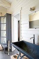 The large wash basin in the bathroom has been imaginatively constructed from an antique zinc trough mounted on a stand made of oak planks