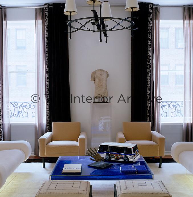Subtle floor lighting illuminates the carpet beneath the pair of contemporary sofas in this small apartment