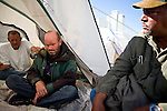 RENO, NV - OCTOBER 6:  Bradford Clark, left, Robert Benson, center, and other homeless men kill time at a tent city for the homeless in downtown Reno, Nevada October 6, 2008. The City of Reno set up the tent city when existing shelters became overcrowded as Nevada struggles with one of the highest unemployment rates in the country. (Photo by Max Whittaker/Getty Images)
