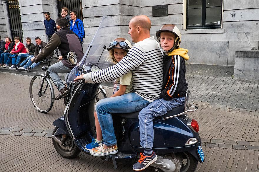 Nederland, Utrecht, 16 juni 2015 <br /> Man op scooter rijdt met twee kinderen door de stad met zijn stinkscooter. Kinderen hebben wel netjes een helm op.<br /> <br /> Foto: Michiel Wijnbergh