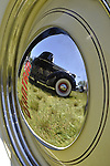 Westbury, New York, USA. June 12, 2016.  A yellow 1948 Bantam Roadster, owned by Wade Jacobs of Mineola, has reflection of nearby vintage black car on its hubcap, at the Antique and Collectible Auto Show at the 50th Annual Spring Meet at Old Westbury Gardens, in the Gold Coast of Long Island, and sponsored by Greater New York Region, GNYR, Antique Automobile Club of America, AACA. Participating vehicles in the judged show included hundreds of domestic and foreign, antique, classic, collectible, and modern cars.