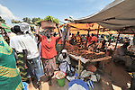 Margaret Dure carries her produce through the market in Yei, Southern Sudan. She and several other women in the market have received support from a microfinance program run by the United Methodist Women in Yei.