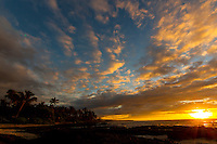 Winter sun rays shine through the clouds on a beach with tide pools in Puako, Big Island.