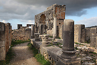 Atrium of the House of the Dog, where a bronze canine statue was found, and the Triumphal Arch of Caracalla behind, built 217 AD by the city's governor Marcus Aurelius Sebastenus in honour of Emperor Caracalla, 188-217 AD, and his mother Julia Domna, Volubilis, Northern Morocco. This house is based around a peristyle courtyard with central pool, around which are the living and sleeping rooms. Here we see its carved Corinthian capitals. Volubilis was founded in the 3rd century BC by the Phoenicians and was a Roman settlement from the 1st century AD. Volubilis was a thriving Roman olive growing town until 280 AD and was settled until the 11th century. The buildings were largely destroyed by an earthquake in the 18th century and have since been excavated and partly restored. Volubilis was listed as a UNESCO World Heritage Site in 1997. Picture by Manuel Cohen