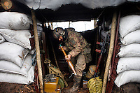 """UKRAINE, 02.2016, Oblast Donetsk. Ukrainian-Russian conflict concerning Eastern Ukraine / Foreign volunteers (""""Task Force Pluto"""") fighting with the far-right militia Pravyi Sektor against the Russian-backed separatists: Ben (Austria) assembles RPG-7 rocket propelled grenade parts in a trench shelter at the Donetsk frontline. © Timo Vogt/EST&OST"""