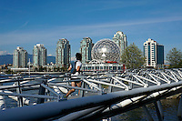 Jogger running across the Canoe Bridge in the Olympic Village area, Vancouver, BC, Canada