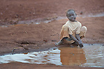 Six-year old Surm Abdala washes her hands in a puddle of muddy water in the Ajuong Thok Refugee Camp in South Sudan. The camp, in northern Unity State, hosts thousands of refugees from the Nuba Mountains, located across the nearby border with Sudan. The ACT Alliance provides a variety of services in the camp.