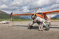 Danielle Terrel and Dirk Nickish fuel Coyote Air De Havilland Beaver airplane, Coldfoot airport, Coldfoot, Alaska.