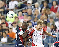New England Revolution defender Jose Goncalves (23) and Toronto FC forward Jeremy Brockie (22) battle for head ball.  In a Major League Soccer (MLS) match, Toronto FC (white/red) defeated the New England Revolution (blue), 1-0, at Gillette Stadium on August 4, 2013.