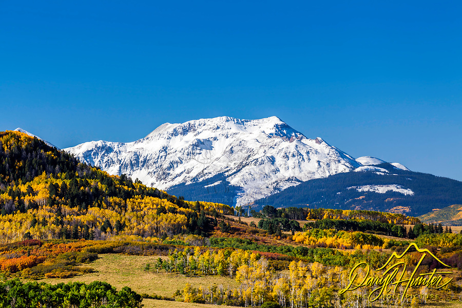 One of the towering peaks of the San Juan Mountain Range crowns the forest of gold, red and orange near Telluride, Colorado.
