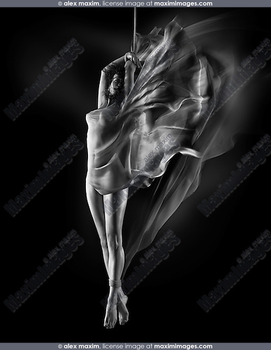 Sensual dynamic dreamy photo of a beautiful nude woman with tied ankles and cloth wrapping her naked body, suspended on a bondage rope by her hands on black background Black and white