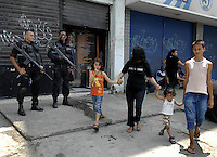 A family runs past policemen taking positions during an operation against drug traffickers in the Complexo da Penha, Rio de Janeiro, Brazil, November 25, 2010. Authorities in Rio de Janeiro try to control a fourth day of violence apparently orchestrated by drug gang members who have attacked police stations and burned cars in Rio de Janeiro city as protest by traffickers after being forced from their turf by police occupations of more than a dozen slums in the past two years..(Austral Foto/Renzo Gostoli)