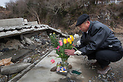 Takashi Sato (55yrs old) lays flowers at the home of his late sister Toshiko, who died in the 2011 tsunami, on the 1 year anniversary of the March 11th 2011 earthquake and tsunami, in Minami-Sanriku, Tohoku region, Japan on Sunday 11th March 2012.