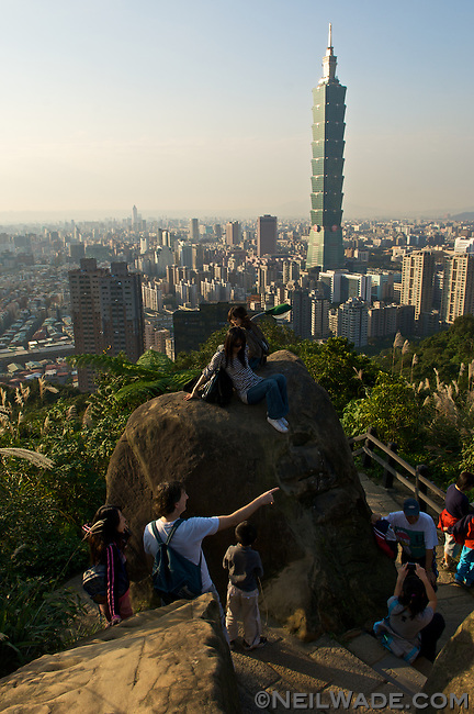 A group of tourists climb a boulder for a good view of Taipei 101 and the Taipei City skyline from Elephant Mountain, Taipei, Taiwan.