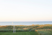 A quirky play on the traditional lifeguard chair, this minimal 'ladder-chair' stands precariously on the edge of the garden looking out to sea