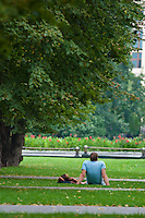 Man with a girl lie on the green grass under the tree in Moscow near the Kremlin wall