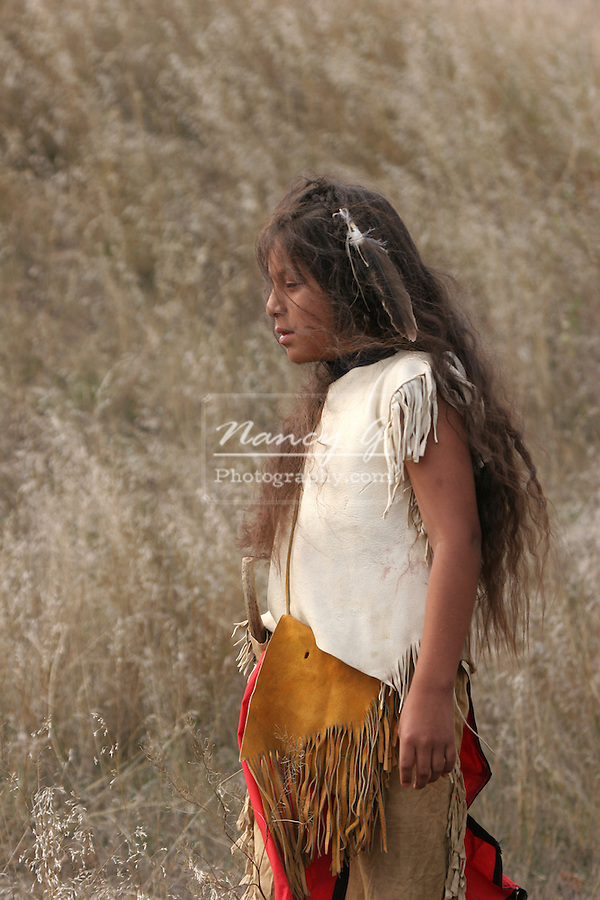 A Native American Indian boy standing in the grass