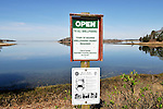 Open to all shellfishing sign and bluecrab regulations signs posted at oceans edge at a  Cape Cod  Harbor on a calm day.