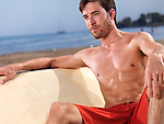 Young man enjoying his time at the beach with a surfboard