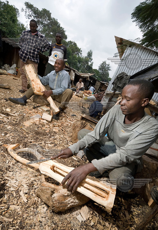 Wood carvers at work in Nairobi, behind him special, tropical hardwood illegally cut from Ngong forest. Ngong forest is a fenced and  protectedsanctuary. It is a nature reserve that has an abundance of animals and wildlife and acts as a physical division between the rich and poor areas of Nairobi. Illegal deforestation is a serious problem as the forest is full of rare, hardwood species that are sold to souvenir carvers in Nairobi who make wooden animals in all sizes for tourists in Kenya.