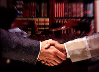 Male female shake hands in lawyers business office.