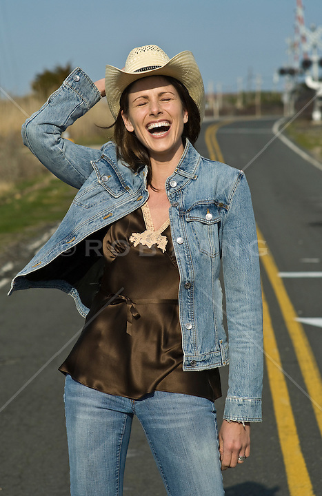 Woman in denim jacket and jeans standing outside on a road laughing