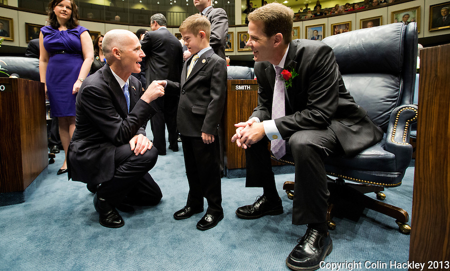TALLAHASSEE, FLA. 3/5/13-OPENING030513CH-Gov. Rick Scott, left, shakes hands with Andrew Gardiner Jr., age 9, son of Sen. Andy Gardiner, R-Orlando, right, during the opening day of the 2013 legislative session Tuesday at the Capitol in Tallahassee, Fla...COLIN HACKLEY PHOTO