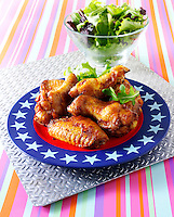 Spicy BBQ Chicken wings and thights on a plate with a blue edge and stars