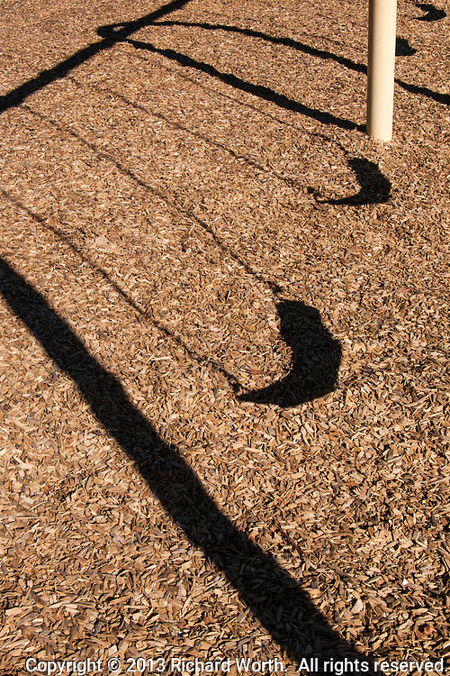 At a neighborhood playground, children's swings cast long shadows on the bark-covered ground.