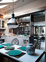 The painted wood kitchen and dark oak table are both custom made: the tabletop is Carrara marble and the table is set with celadon plates and 1950s glasses