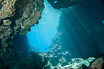 Paradise Reef, Taveuni, Fiji; sun rays stream through the shallow water at the opening to an underwater cavern created lava tubes