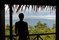 Woman on a balcony looking out over Lake Peten Itza at Tikal, Guatemala