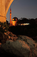 Koski Mehmed Pasha mosque, built 1618, lit up at night, seen from under the Stari Most or Old Bridge, a 16th century Ottoman bridge over the Neretva river, in Mostar, Bosnia and Herzegovina. The town is named after the mostari or bridge keepers of the Old Bridge. Mostar developed in the 15th and 16th centuries as an Ottoman frontier town and is listed as a UNESCO World Heritage Site. Picture by Manuel Cohen