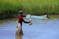 Young man in the water throwing his fishing net near Mexcaltitan Mexico