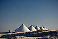 A row of tents is lined up along the beach overlooking the sea