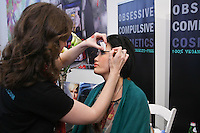 Obsessive Complusive Cosmetics, makeup artist applies makeup on woman, at the Makeup Show NYC, in the Metropolitan Pavilion, May 15 2011.