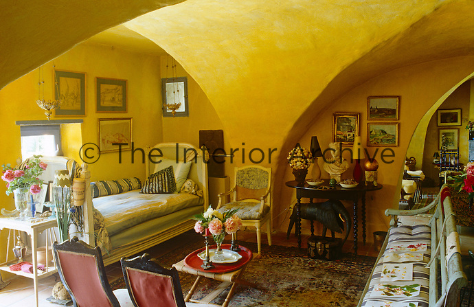 The salon is arranged in traditional Provencale style with a daybed, banquette, armchairs and small tables dotted about