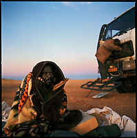 Sahara desert, Libya-Chad, November/December 2004..Every week, a convoy of 40 privately owned Libyan trucks loaded by the WFP with about 1000 metric tons of western food aid cross 2500 km of deep desert across Libya and Chad to reach more than 200 000 refugees from Darfur in camps near the Sudanese border. A mechanic recites verses from the Coran in the freezing morning...