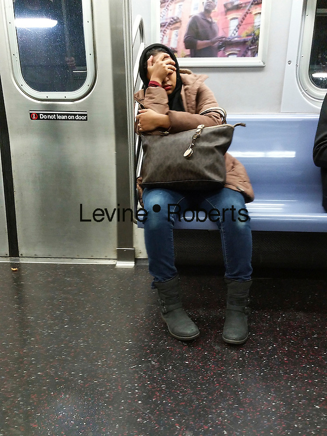 A tired rider on the subway in New York on Friday, November 11, 2016. (© Richard B. Levine)