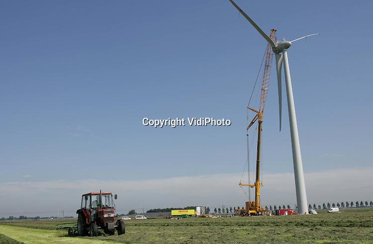 Foto: VidiPhoto..ECHTELD - De Duitse uitvoerder Enercon plaatst woensdag een rotor op een enorme windmolen langs de A15, terwijl melkveehouder Van Dee uit IJzendoorn gewoon doorgaat met zijn hooiwerkzaamheden. Op die plek verreist op dit moment Windpark Echteld, met vier turbines van 78 meter hoog en een vermogen van 2 megawatt. Daarmee behoren ze tot de grootste windturbines van Nederland. Opdrachtgever is WEOM/NUON. De bouwkosten bedragen 10-12 miljoen euro. Eén van de molens komt op het land van Van Dee.