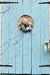 Closeup of picturesque Cape Cod barn door with decorated straw hat on door.