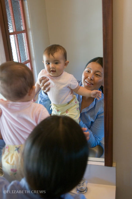 Berkeley CA Nepalese mother helping daughter seven-months-old explore her image in mirror  MR