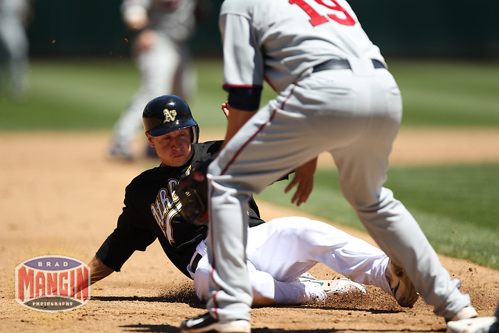 OAKLAND, CA - JUNE 6:  Mark Ellis #14 of the Oakland Athletics slides safely into third base during the game against the Minnesota Twins at the Oakland-Alameda County Coliseum on June 6, 2010 in Oakland, California. Photo by Brad Mangin