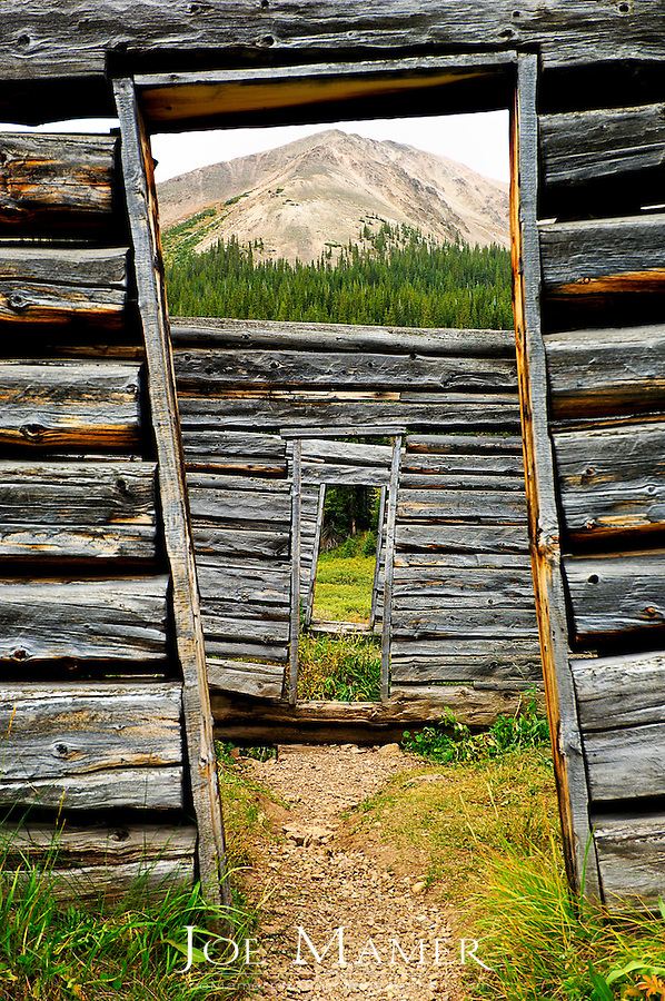 Looking through doors of a log cabin towards mountain in the distance at Independence ghost town.