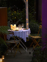 A small table set for a romantic dinner for two in a decked corner of the garden surrounded by tealights