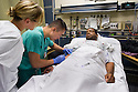 St. Mary's Medical Center. Vincent Kan, class of 2014, in green scrubs, and patient, release 20120524008. nurse unknown.