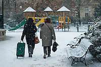 Women walking through a Paris park in the snow, one pulling a shopping trolley.