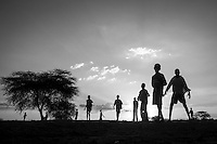 Kakuma, Kenya: Refugee children gather on the open fields at the entrance of the camp to play soccer as the sun sets.